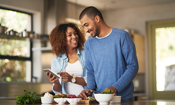 Young couple looking at phone in kitchen