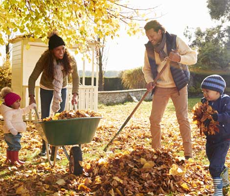 two small children help parents rake leaves in their yard