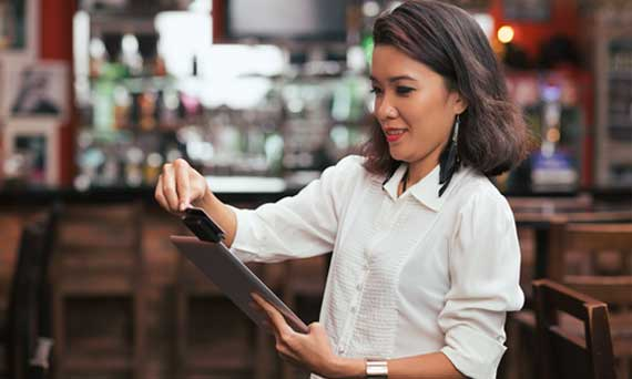 bar owner swipes card using a payment processing tool on their iPad