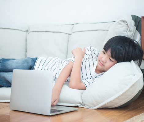 child uses laptop unattended while lounging at home
