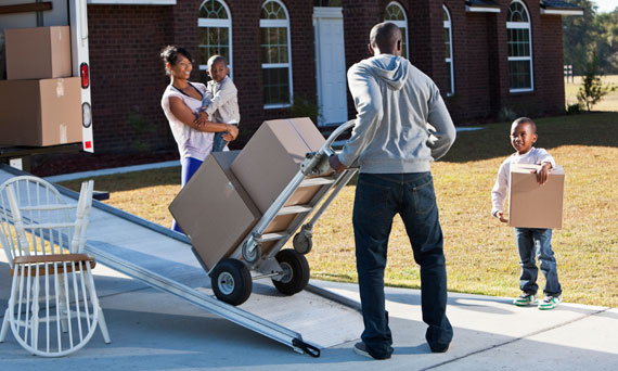 family unpacks a moving truck outside of their new home