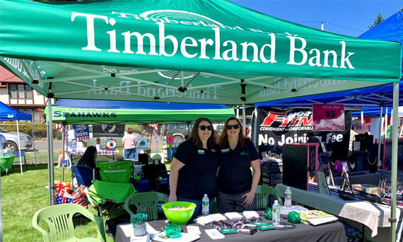 Employees pose for a photo at the Timberland Bank tent at the Edgewood Community Picnic