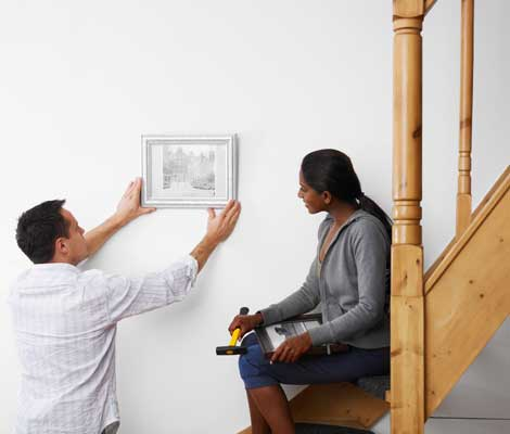 Couple hangs up a painting while decorating their new home