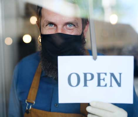business owner wearing a mask smiles while putting the open sign on their window