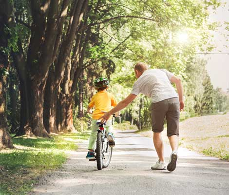 father teaches son to ride a bike outside of their home