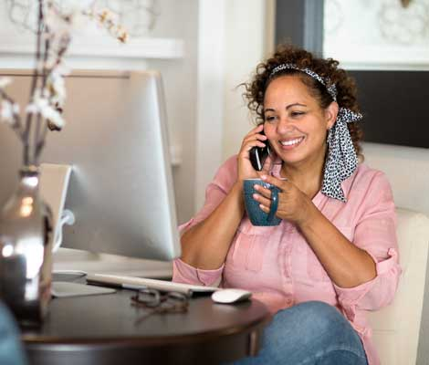 woman talks on the phone while working on the computer and drinking coffee